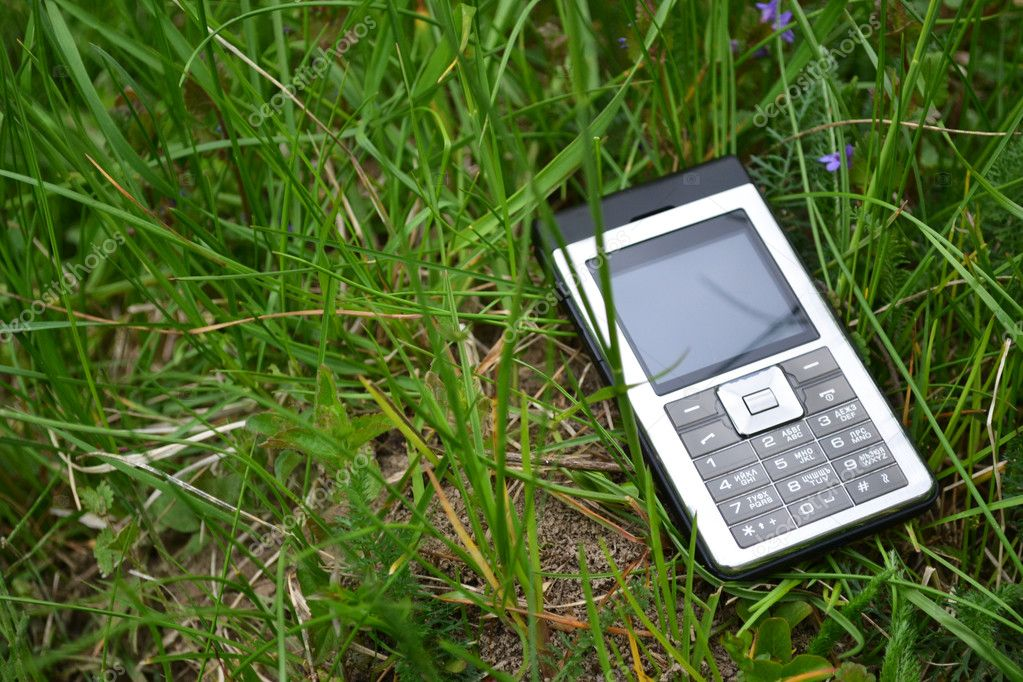 Mobile Phone in green grass. Communication bacground. — Stock Photo #5640306