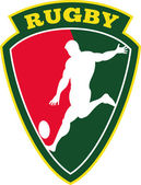 Rugby player kicking ball shield — Stock Photo