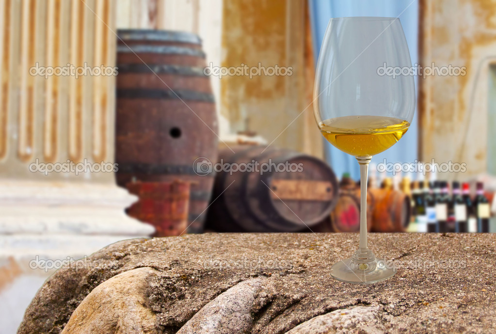 A glass of white wine with barrels and bottles in the background  Stock Photo #5934572