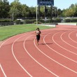 Young black woman running on track long shot — Stock Photo