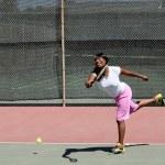 Smiling black woman swinging tennis racket on court — Stock Photo