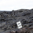 Road Closed sign surrounded by black lava — Stock Photo