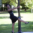 Young black woman in dress holdig on to pole — Stock Photo