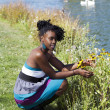 Young black woman squatting by flowers park - Stok fotoğraf