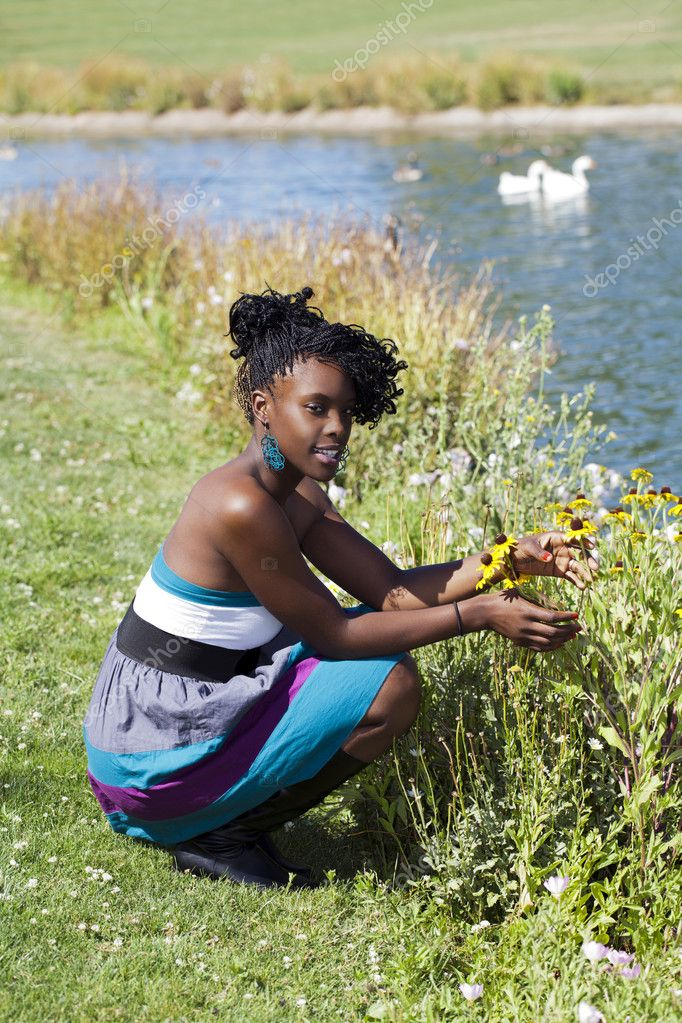 Young black woman outdoors squatting at park  Stock Photo #6303618
