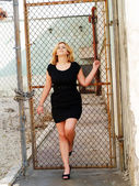 Young plump caucasian woman black dress cyclone fence — Stock Photo
