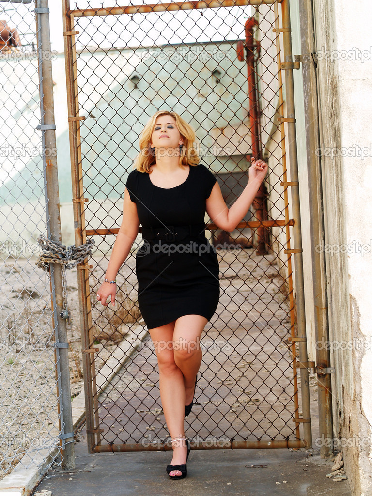 Young caucasian woman leaning against gate black dress — Stock Photo #6537180