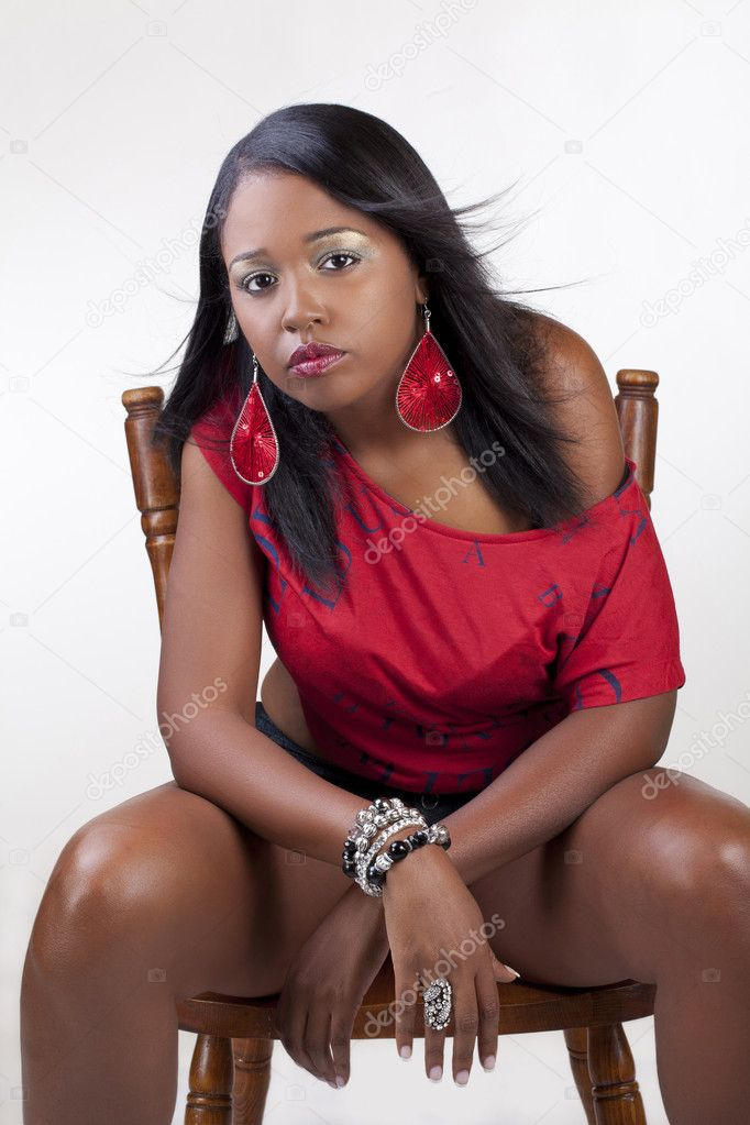 Young African American woman sitting on chair red top  Stock Photo #6537196