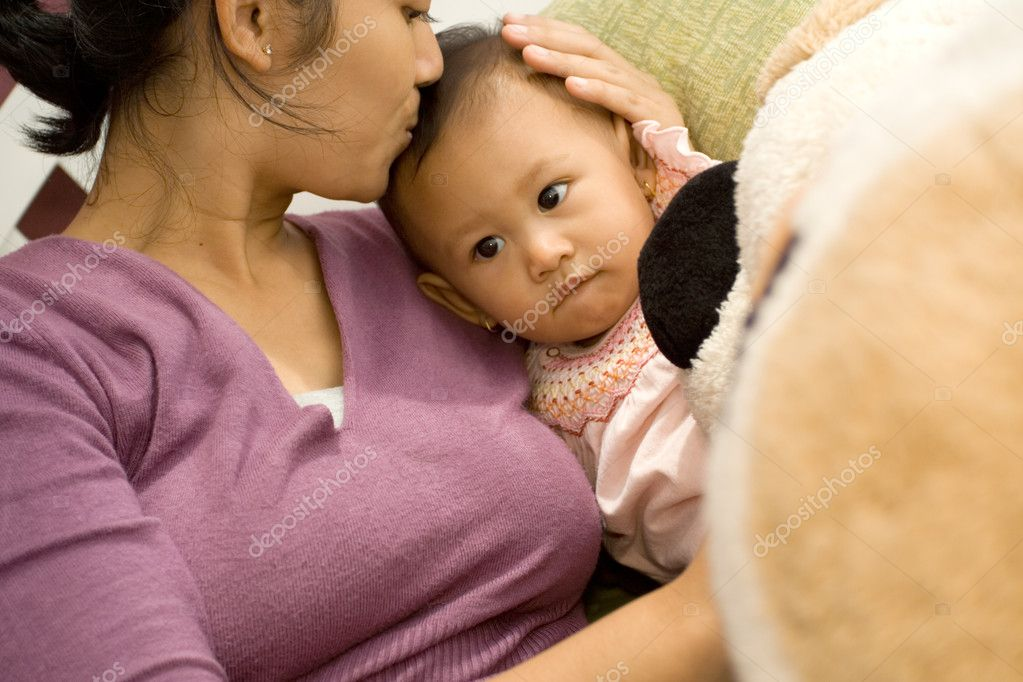Asian ethnic mother expressing kissing baby daughter  Stock Photo #6336556