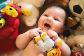 Smiling baby surrounded by toys — Stock Photo