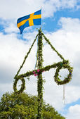 A traditional swedish midsummer pole with a swedish flag — Stock Photo