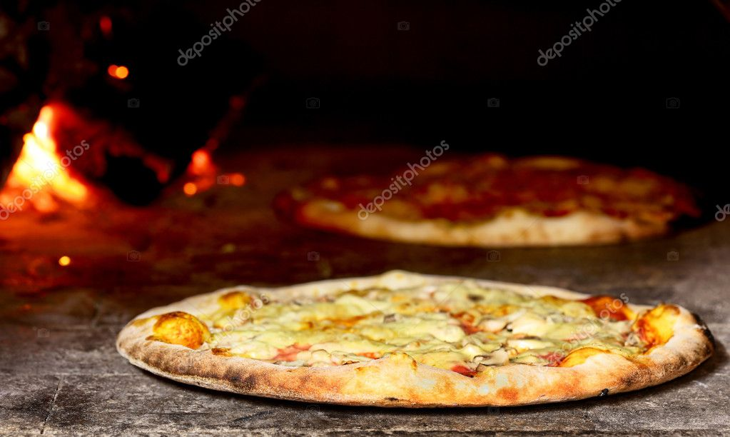 Delicious pizza baking in wood fired oven — Stock Photo #5388127