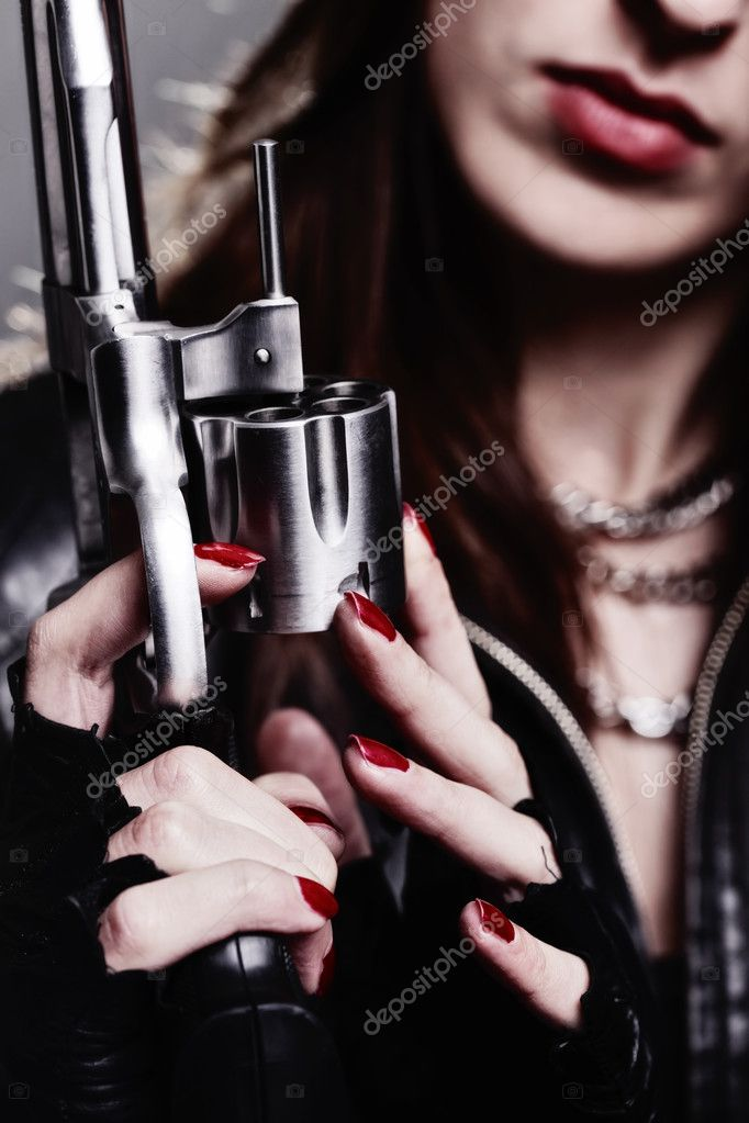 Rebel girl with motorcycle gloves holding a revolver — Stock Photo #5988625