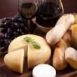 Cheese, wine and other tasty stuff on wooden table — 图库照片
