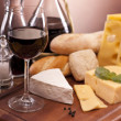 Cheese, wine and other tasty stuff on wooden table — Stock Photo