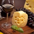 Cheese, wine and other tasty stuff on wooden table — Stock Photo #6168374