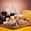 Cheese, wine and other tasty stuff on wooden table — Stock Photo #6168388