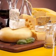 Cheese, wine and other tasty stuff on wooden table — Stock Photo #6168398