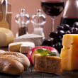 Cheese, wine and other tasty stuff on wooden table — Стоковая фотография