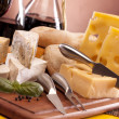 Cheese, wine and other tasty stuff on wooden table — Stock Photo #6168517