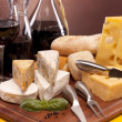 Cheese, wine and other tasty stuff on wooden table — Stock Photo #6168522