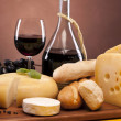 Cheese, wine and other tasty stuff on wooden table — Stock Photo #6168531