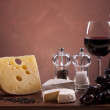 Cheese, wine and other tasty stuff on wooden table — Stockfoto