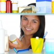 Woman Looking in Medicine Cabinet - Foto Stock