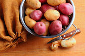 Potatoes in Colander with Burlap Sack and Paring Knife — Stock Photo