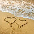 Two hearts drawn in beach in sunset — Stock Photo