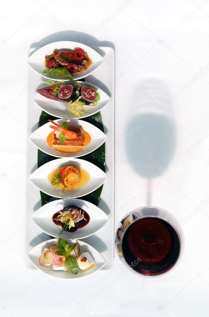 Set of snack and red wine glass on a white table — Stock Photo #6028317