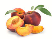 Peach and a half and leaves — Stock Photo