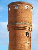 Old red brick water tower over blue sky — Stock Photo