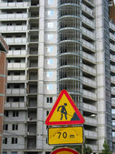 Under construction road sign on building house background — Stock Photo