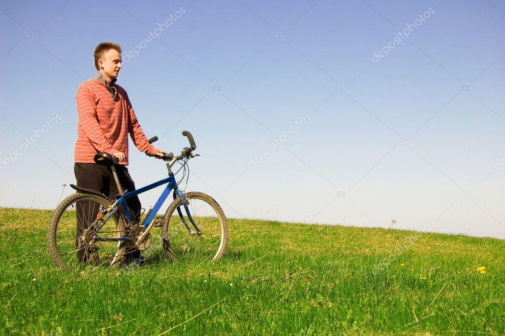 骑自行车的在绿色的原野上看风景
