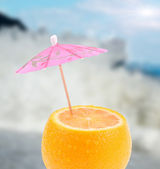 Lemon with umbrella with blurred sea background — Stock Photo