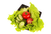 Green salad, tomatoes and cucumber isolated on the white background — Stock Photo
