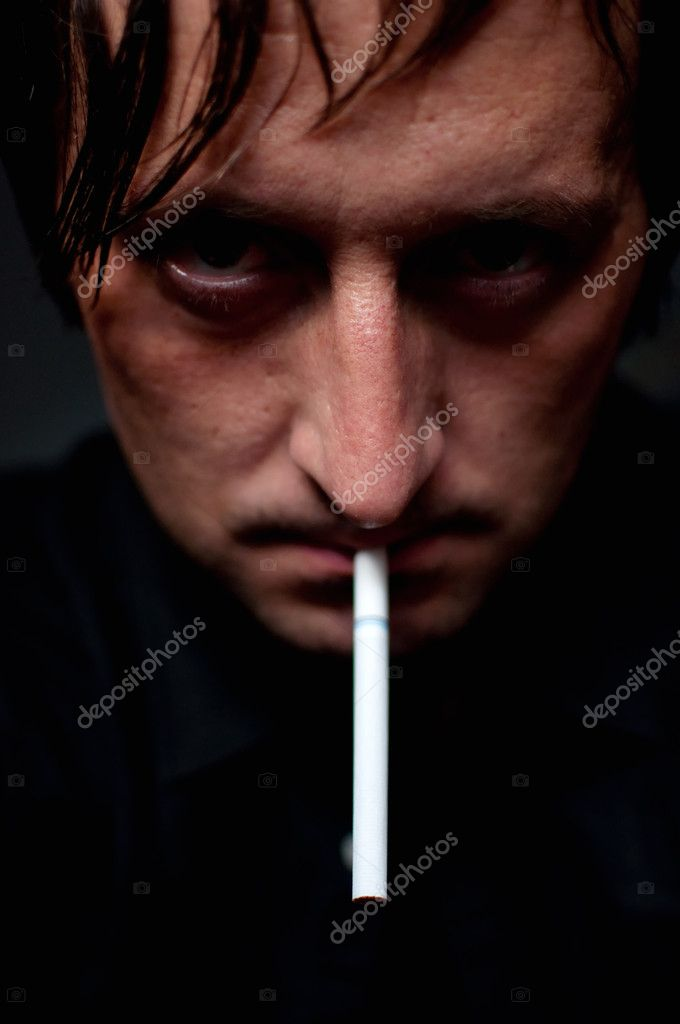 Man smoking cigarette over black background, low key light image — Stock Photo #6015231