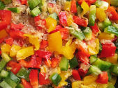 Yellow, red and green Bulgarian pepper in skillet. Slicing. Cubes. — Stock Photo
