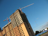 A building site, a hoisting crane and unfinished walls on the blue sky back — Stock Photo