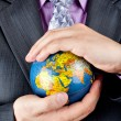 Businessman carrying world globe — Stock Photo
