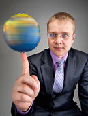 Businessman spinning the world globe on finger — Stock Photo