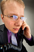 Bizarre businessman talking by phone — Stockfoto