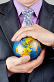 Businessman carrying world globe — Stock Photo