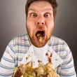 Dirty man chewing hamburger - Stock Photo
