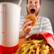 Expressive man eating fast food - Foto Stock
