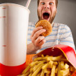 Expressive man eating fast food - Stok fotoğraf