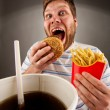Expressive man eating fast food — Stock Photo #5590533