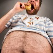 Fat man eating burger - Photo