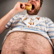 Fat man eating burger - Stockfoto